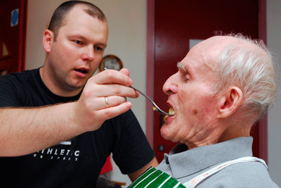 Carer feeding older man